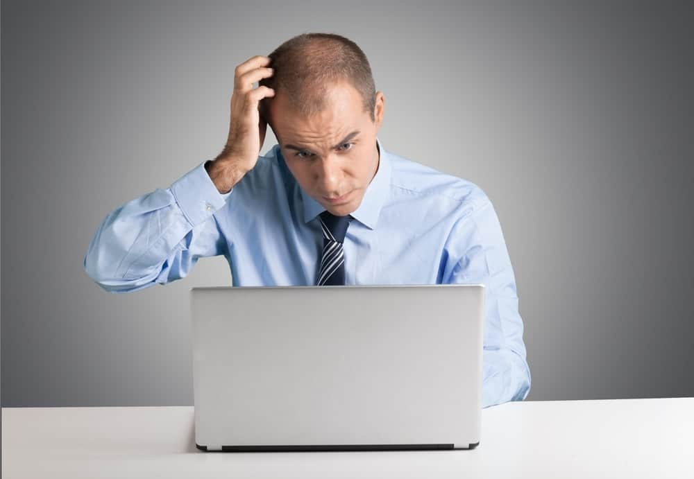 confused man scratching his head while working on a computer